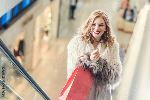 happy stylish women with shopping bag on escalator at mall