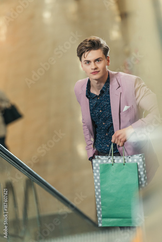 stylish man on escalator with bags at shopping mall