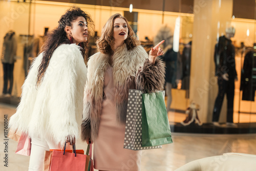 fashionable multiethnic women holding paper bags and pointing with finger in shopping mall