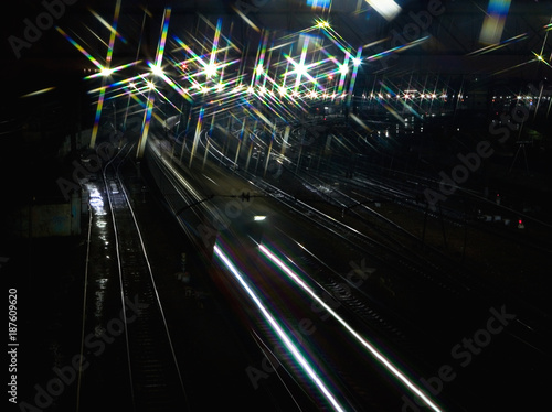 The train rushes on the rails at night. - 187609620