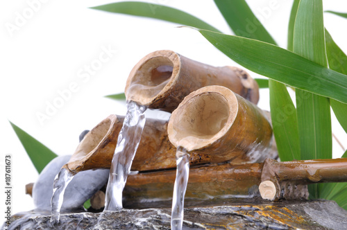 water flowing from litte bamboo fountain on white background