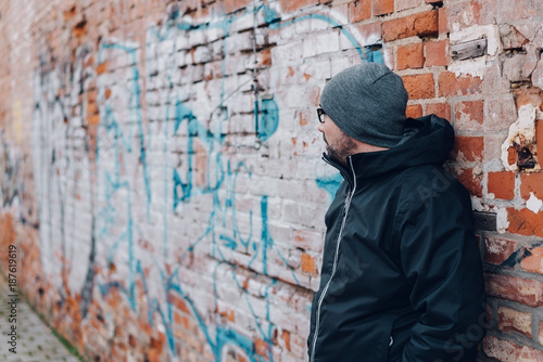 Aluminium Graffiti Man waiting against a graffiti covered wall