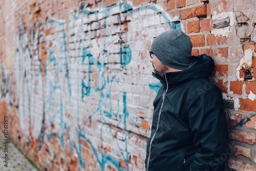 Staande foto Graffiti Man waiting against a graffiti covered wall