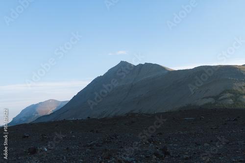 Fotobehang Ochtendgloren Mountains lighten by sunrise and glacier field in shadow in Jasper