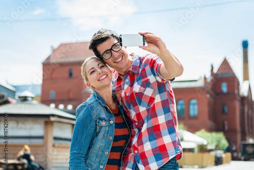 Aluminium Berlijn Tourist couple, woman and man, taking holiday selfie on rooftop in Berlin