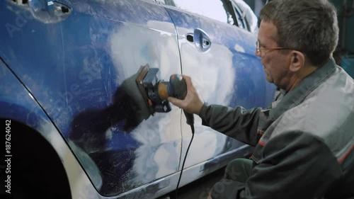 Car mechanic sanding car