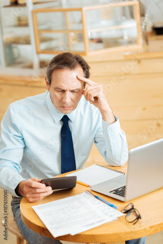 Minute of concentration. Deep thoughtful busy man spending work time in his cafe making calculations and using the laptop. - 187630061