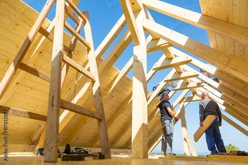 Roof builders mounting prefabricated wooden roof construction. Construction industry concept. - 187632693