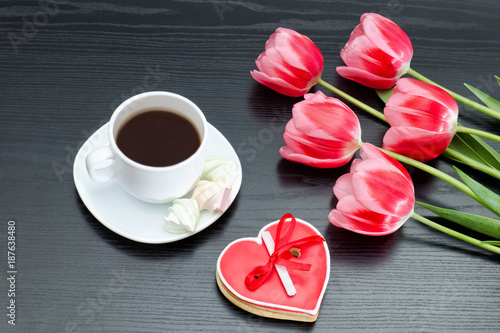 Mug of coffee and heartshaped gingerbread, five pink tulips. Black background.