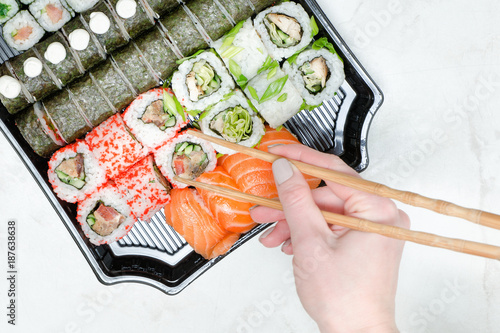 Foto op Canvas Sushi bar Female hand with chopsticks and sushi set. Yellow background. Top view