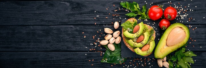 Sandwich with avocados and almonds. On a wooden background. Top view. Free space for your text.