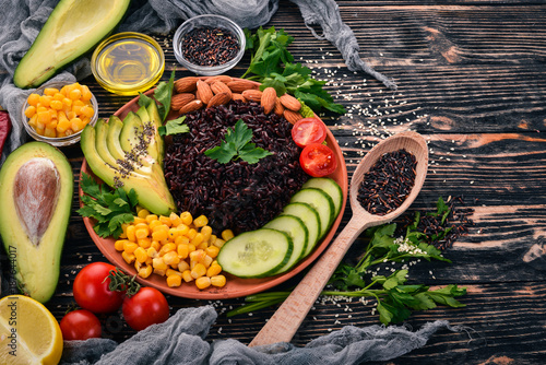 Black rice, avocado, cucumber, corn and almonds. On a wooden background. Top view. Free space for your text. - 187644017