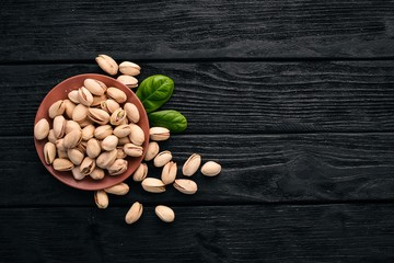 Pistachio nuts on a dark wooden background. Healthy snacks. Top view. Free space for text.