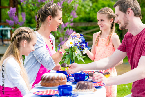 Foto Murales Happy family having coffee time in garden eating cake