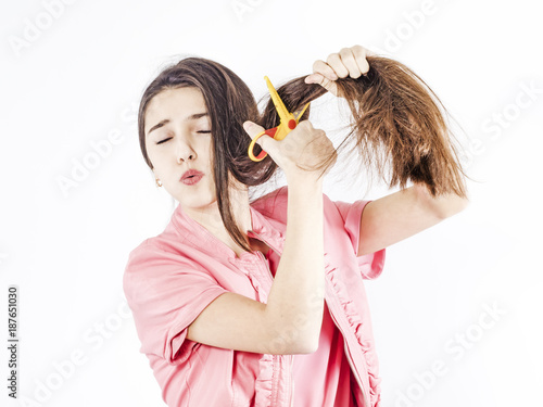A young girl is ready to cut her hair with scissors