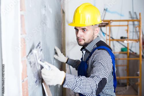 Smiling man in the helmet is plastering the wall © JackF