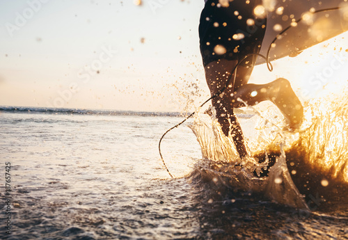 Foto op Canvas Snelle auto s Man surfer run in ocean with surfboard. Closeup image water splashes and legs, sunset light