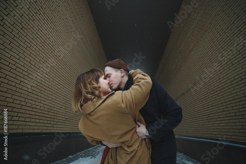 Foto Murales Stylish couple embracing and kissing in tunnel of brick walls. Winter snowy weather. Street love