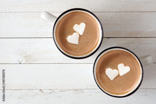 Foto op Canvas Chocolade Two cups of hot chocolate with heart shaped marshmallows over a white wood background