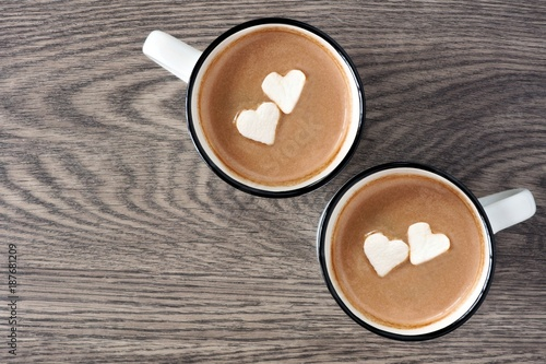 Papiers peints Chocolat Two cups of hot chocolate with heart shaped marshmallows over a wooden background