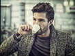 Attractive Man Drinking Coffee while Sitting in a Bar with Serious Expression