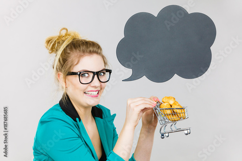 Foto Murales Bussines woman holding shopping cart with sweet bun