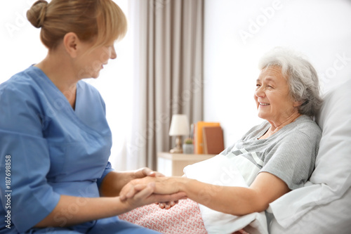 Caregiver massaging hand of senior woman at home © Africa Studio