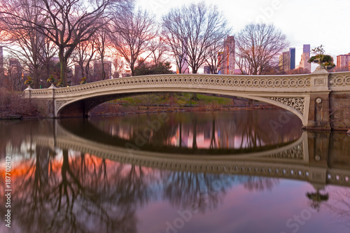 Foto Murales The Bow Bridge at beautiful winter sunrise in Central Park, New York City. The largest park bridge with reflection decorated by planting urns.