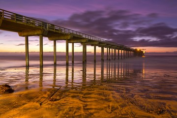 Scripps Pier Sunset Colors and La Jolla Shores Beach with distant Pacific Ocean on the Horizon north of San Diego California