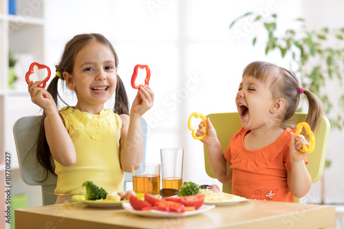 Funny children girls eating healthy food. Kids lunch at home or kindergarten.