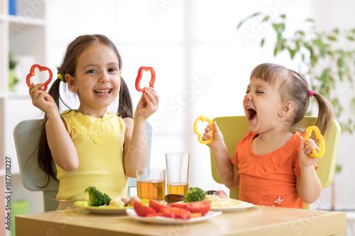 Foto Murales Funny children girls eating healthy food. Kids lunch at home or kindergarten.