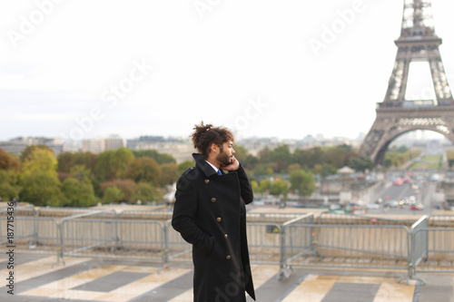 Brazilian male model calling photographer close to Eiffel Tower