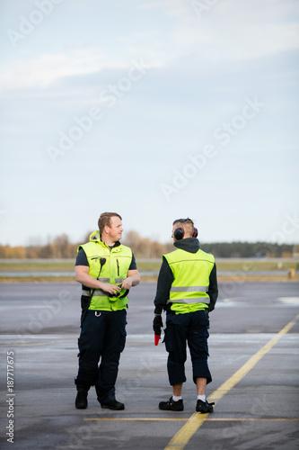 Foto Murales Workers In Reflective Jackets Standing On Airport Runway