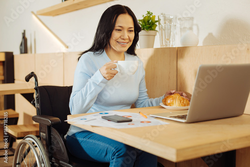 Tea break. Beautiful happy dark-haired crippled woman sitting in a wheelchair and holding a cup of coffee and working on her laptop in a cafe