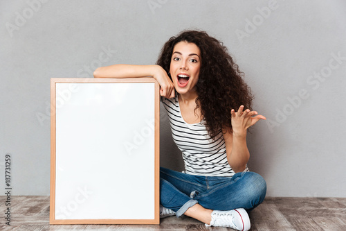 Young gorgeous female in jeans and t-shirt sitting in lotus pose on the floor with big great painting feeling excitement over grey wall copy space