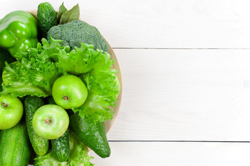 White wooden background with various fresh raw green vegetables and fruits