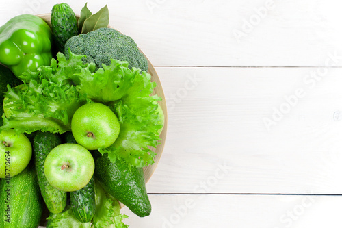 Foto Murales White wooden background with various fresh raw green vegetables and fruits