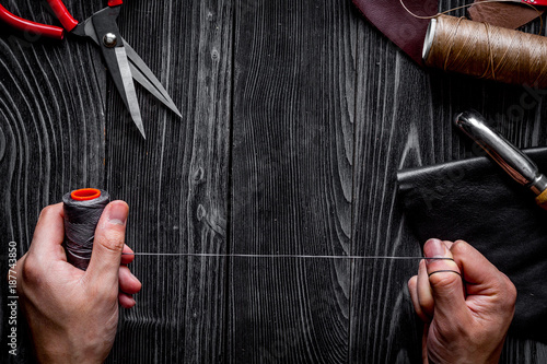 Foto Murales work in leather shop on dark wooden background top view