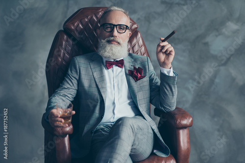 Leinwandbild Motiv Cool man in glasses, hold cigarette,  glass with brandy, in formal wear, tux with red bowtie and pocket square, sit in leather chair over gray background, looking to the camera, shares, stock, money