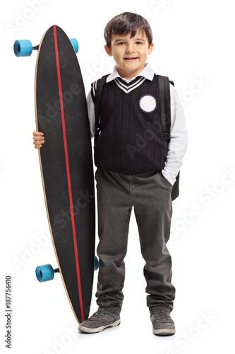 Little schoolboy holding a longboard