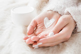Beautiful groomed woman's hands with cream jar on the fluffy blanket. Moisturizing cream for clean and soft skin in winter time. Heart shape created from cream. Love a body. Healthcare concept. - 187758243