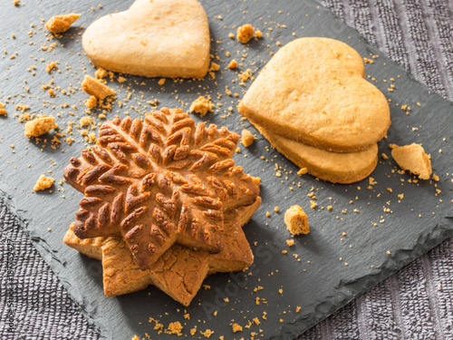 Foto Murales Yellow ginger biscuits in the shape of snowflakes and hearts on a black background