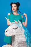 Beautiful girl in a bright dress with a unicorn on a blue background. - 187760620