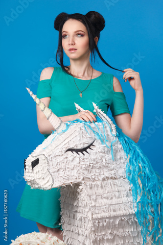Foto Murales Beautiful girl in a bright dress with a unicorn on a blue background.