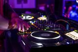 dj mezclando en discoteca fiesta de techno luces de colores botones y plato