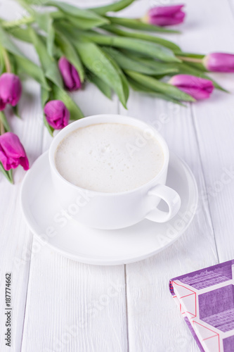White cup with coffee cappuccino, book and purple tulips on a white background. Free space - 187774662