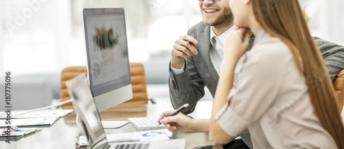 Manager and accountant are sitting and discussing financial charts with the profits of the company in the workplace