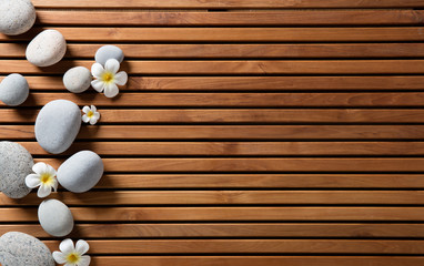 zen pebbles and spa flowers set on hammam wooden board © STUDIO GRAND WEB
