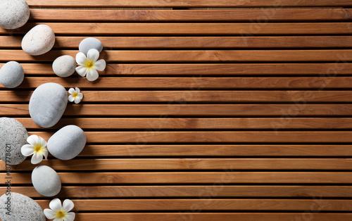 zen pebbles and spa flowers set on hammam wooden board © STUDIO GRAND WEB