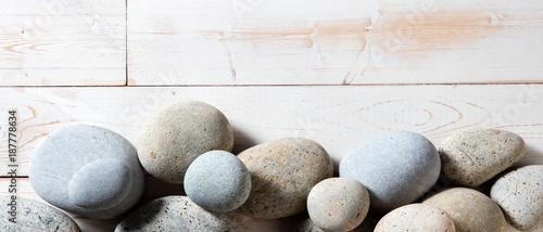 border of grey zen stones set on white wooden background